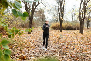Photo of young woman runner in warm clothes and earphones running in autumn park