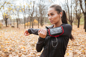 Photo of young woman runner in warm clothes and headphones looking aside in autumn park while make sport exercise