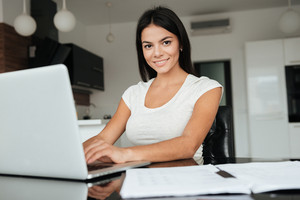 Photo of young woman typing by laptop and analyzing home finances. Look at camera.