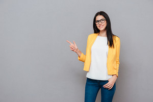 Photo of young woman wearing eyeglasses and dressed in yellow jacket pointing over grey background. Look at camera.