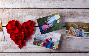 Photos of a romantic senior couple laid on white wooden table. Red rose petal heart. Valentines day composition.