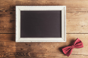 Picture frame and a bow tie on wooden background.