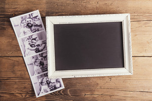 Picture frame and instant photos on wooden background.