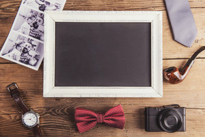 Picture frame, instant photos and various objects on wooden background.