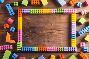 Picture frame made of colorful blocks laid on wooden background.