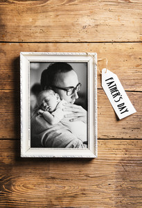 Picture frame with black and white picture of father holding his baby son in the arms. Fathers day concept. Studio shot on wooden background.