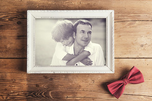 Picture frame with family photo and dotted bow tie laid on wooden background.