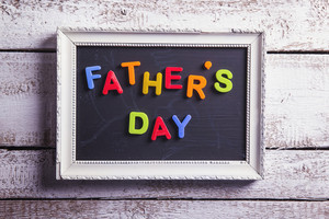 Picture frame with Fathers day sign laid on wooden floor background.