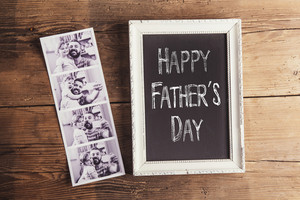 Picture frame with Happy fathers day sign and instant photos on wooden background.