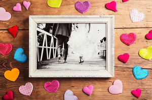 Picture frame with wedding photo. Studio shot on wooden background.