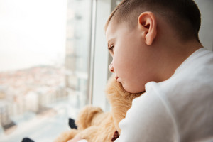 Picture of alone little sad boy with teddy bear near window waiting for parents at home. Look at window.