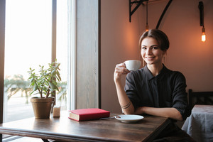 Picture of amazing cheerful young woman sitting at the table in cafe and looking at camera while drinking coffee.