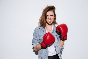 Picture of angry lady boxer dressed in jeans jacket and gloves standing isolated over white background.