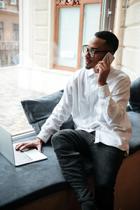 Picture of attractive african businessman wearing glasses sitting near window and typing by laptop computer while talking by phone. Coworking.