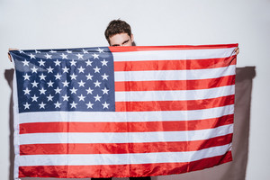 Picture of attractive man posing at studio and look at camera while holding USA flag. Isolated over white background.