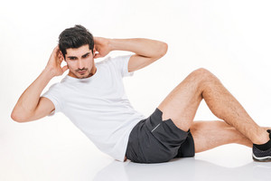 Picture of attractive sportsman in gym make sports exercises on floor over white background.