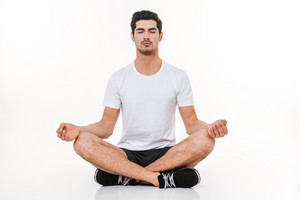 Picture of attractive sportsman in gym sitting on floor over white background. Eyes closed. Yoga concept.