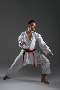 Picture of attractive sportsman in kimono practice in karate isolated over grey background. Looking aside.