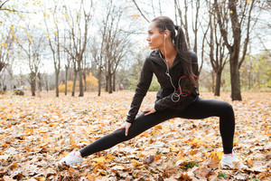 Picture of attractive woman runner in warm clothes and headphones looking aside in autumn park while make sport exercise