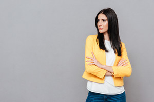 Picture of attractive young woman dressed in yellow jacket posing over grey background with arms crossed while looking at copyspace.