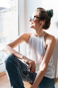 Picture of attractive young woman wearing glasses sitting near window at the home listening music. Look at window.
