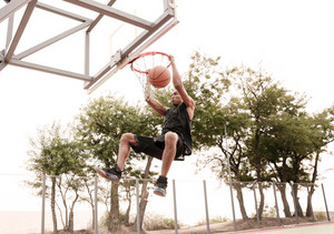 Picture of basketball player practicing for basketball and jumping to hoop. Looking at basketball hoop.
