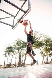 Picture of basketball player practicing for basketball. Looking at basketball hoop.