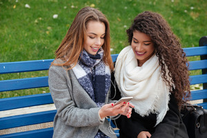 Picture of beautiful ladies sitting on a bench and smiling while listening music together on earphones. Horizontal shot. Looking at phone. With grass on background.