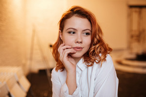 Picture of beautiful redhead young woman dressed in white shirt looking aside with hand touching her face
