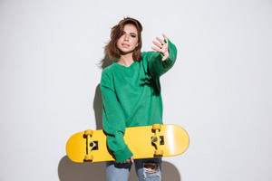 Picture of beautiful skater lady dressed in green sweater standing isolated over white background with skateboard.