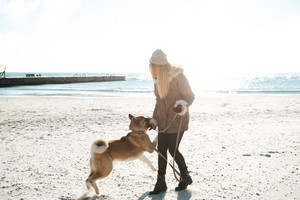 Picture of beautiful young girl walks in winter beach with dog on a leash.