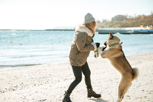 Picture of beautiful young lady walks in winter beach with dog on a leash.