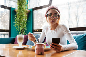 Picture of beautiful young lady wearing hat and glasses using phone drinking coffee while sitting in cafe.