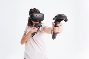 Picture of beautiful young lady wearing virtual reality device holding joysticks over white background.