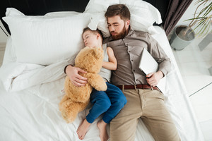 Picture of boy sleeping at home in bed with his bearded father and toy.