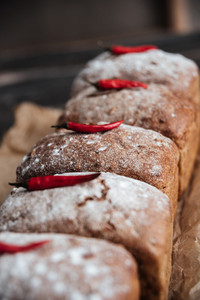 Picture of bread with flour and pepper on dark wooden table at bakery