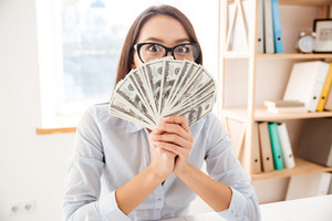 Picture of businesswoman dressed in white shirt sitting in her office and holding money in hand near face