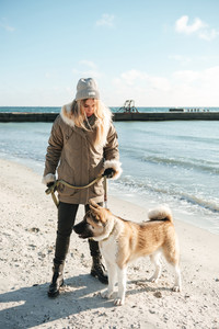 Picture of caucasian young lady walks in winter beach with dog on a leash.