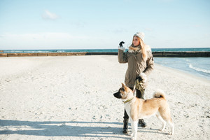 Picture of caucasian young woman walks in winter beach with dog on a leash.