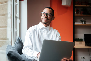 Picture of cheerful african businessman wearing glasses sitting near window and typing by laptop computer. Coworking.