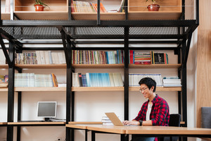 Picture of cheerful asian male dressed in shirt in a cage and wearing glasses using laptop at the library. Looking at the laptop.