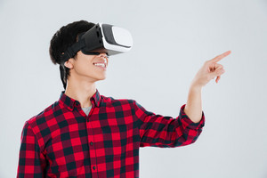 Picture of cheerful asian man dressed in casual shirt in a cage and wearing virtual reality device and pointing right. Isolated over white background.