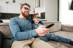 Picture of cheerful bearded father holding remote control while watching TV with his little cute son using 3d glasses.