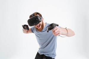 Picture of cheerful bearded man wearing virtual reality device standing over white background with joysticks
