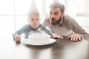 Picture of cheerful bearded young father sitting near birtday cake with his little son.