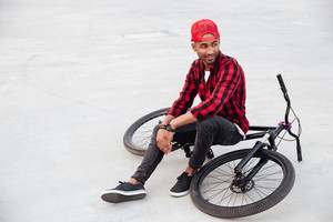 Picture of cheerful dark skinned guy wearing cap sitting on his bicycle. Against nature background.