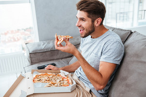 Picture of cheerful hangry young man eating pizza while sitting on sofa and watching TV.