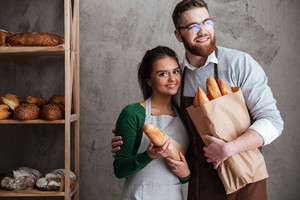 Picture of cheerful loving couple bakers holding bread in hands. Woman looking at camera.