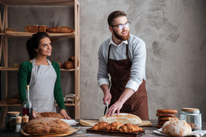 Picture of cheerful loving couple bakers. Man cut the bread. Looking aside.