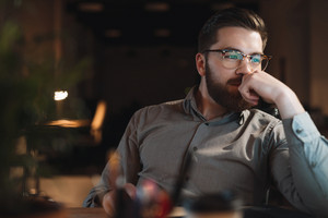 Picture of cheerful web designer dressed in shirt and wearing eyeglasses working late at night and looking at computer.